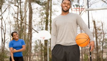 Sports: Young African descent couple play basketball at ourdoor park.