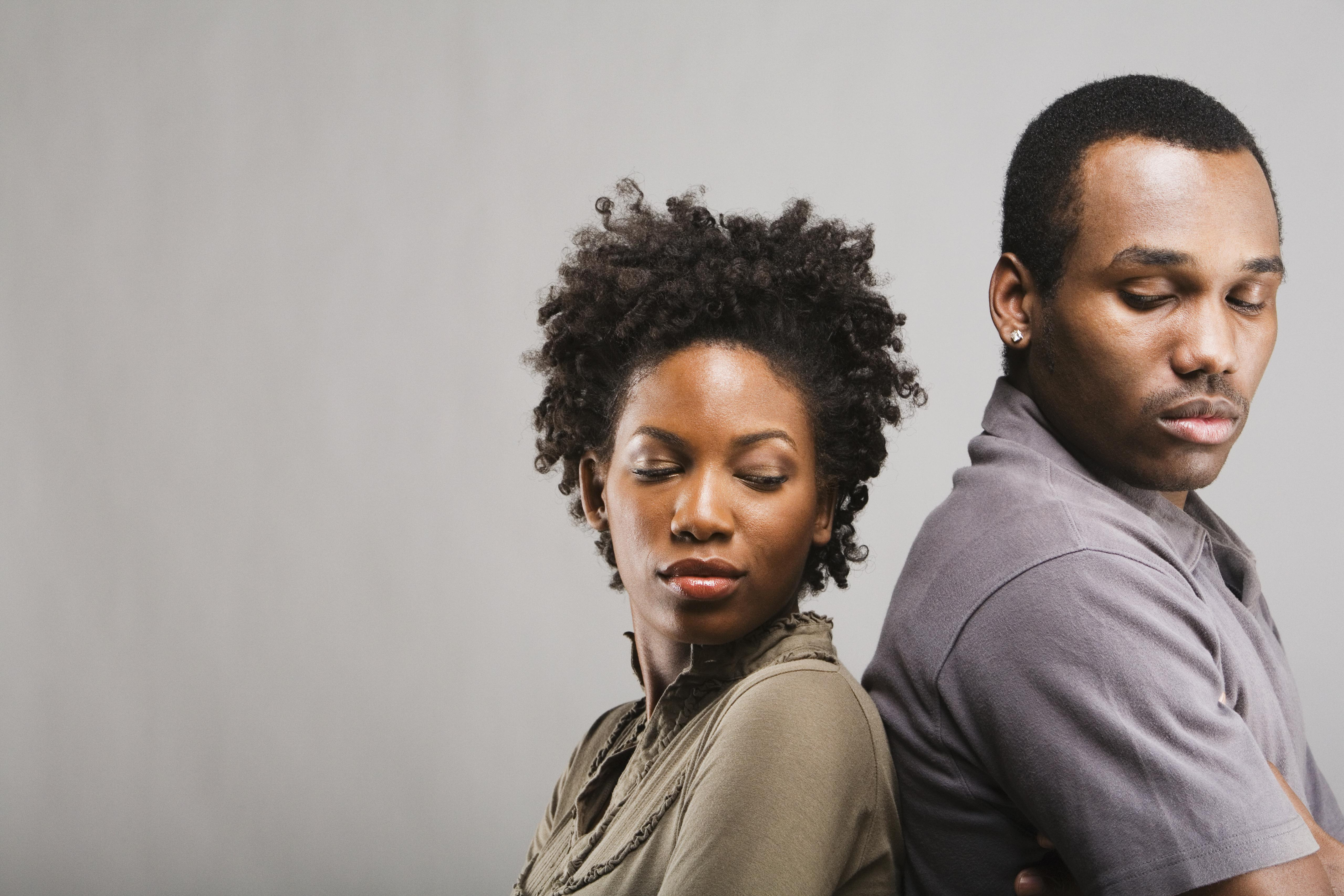 Angry African American couple standing back to back