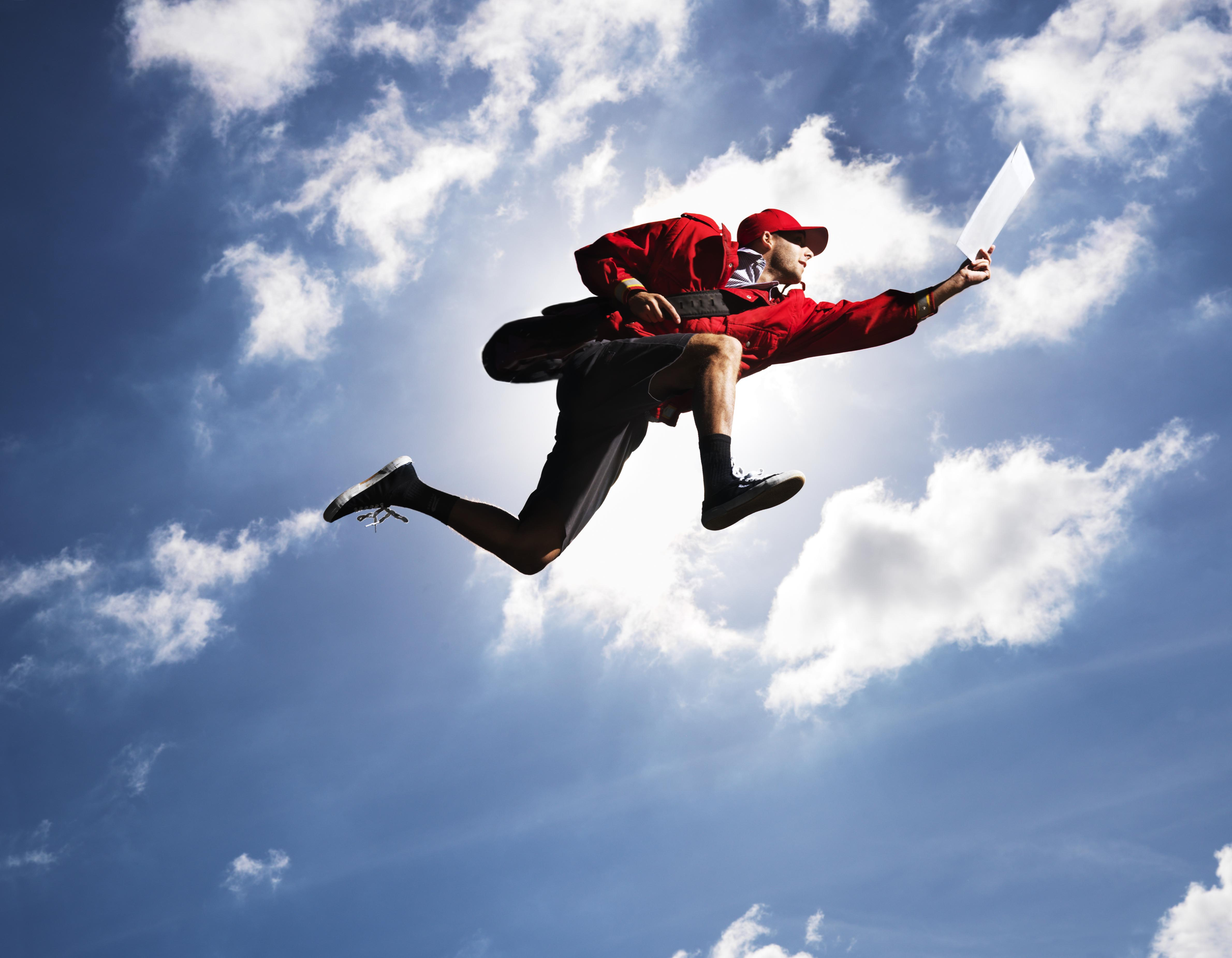 Man flying in air with letter in hand, against sky, low angle view