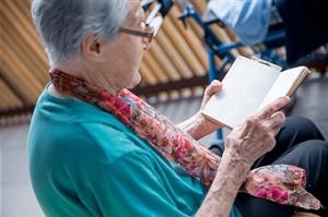 Senior Woman Reading Book On Balcony At The Elderly Center