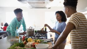 African American mother and teenage sons cooking at stove in kitchen