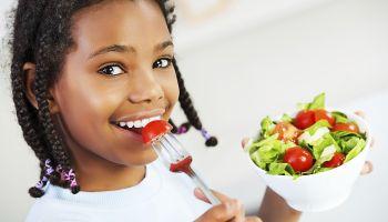 Little girl eating vegetable salad.
