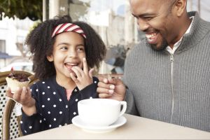 Little girl enjoying a cupcake with her dad.