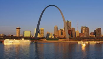 This is the skyline at sunrise. It is situated along the Mississippi River. There are riverboats on the water with the St. Louis Arch in clear view.
