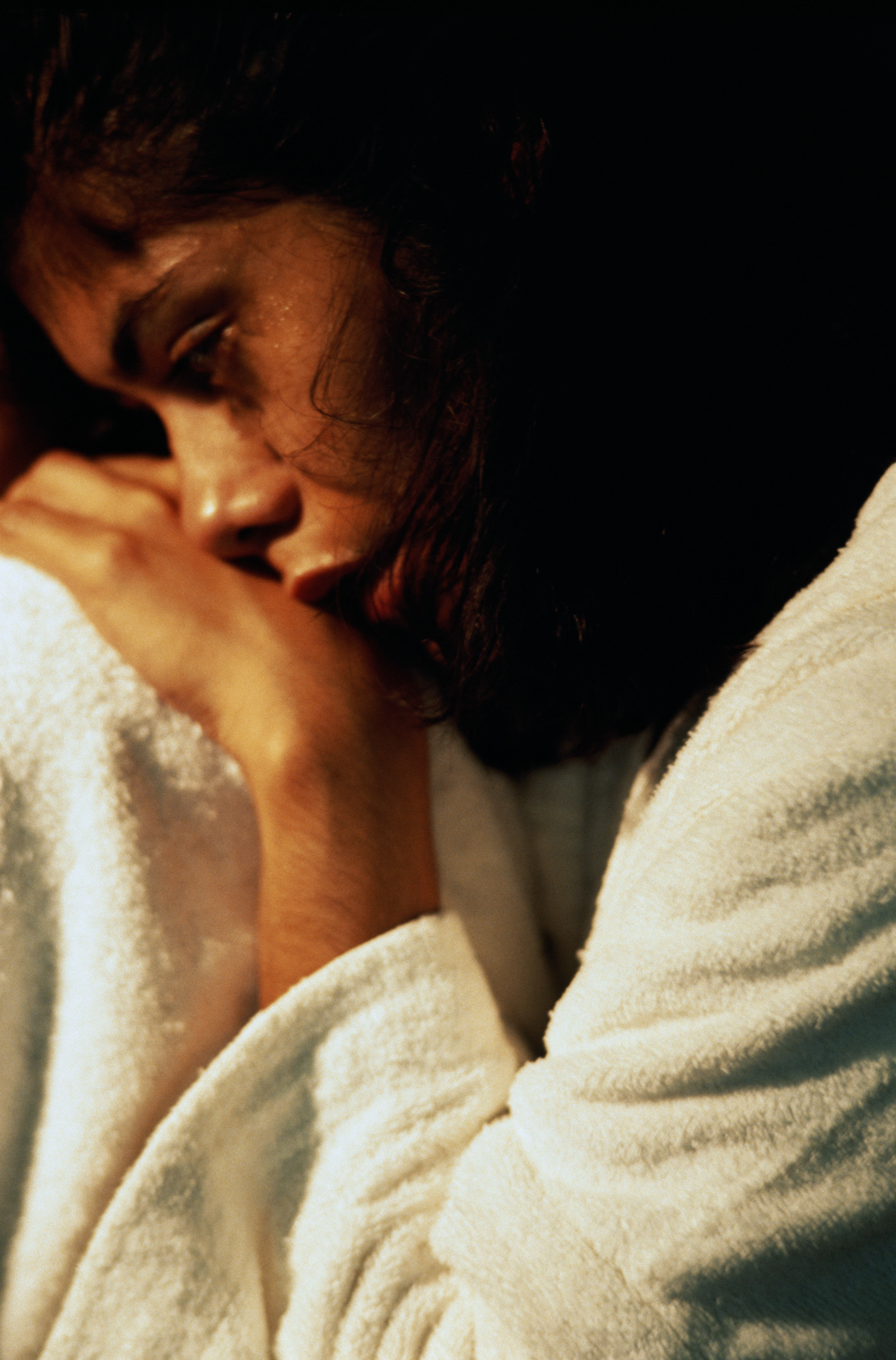 Woman in white bathrobe curled up and looking pensive