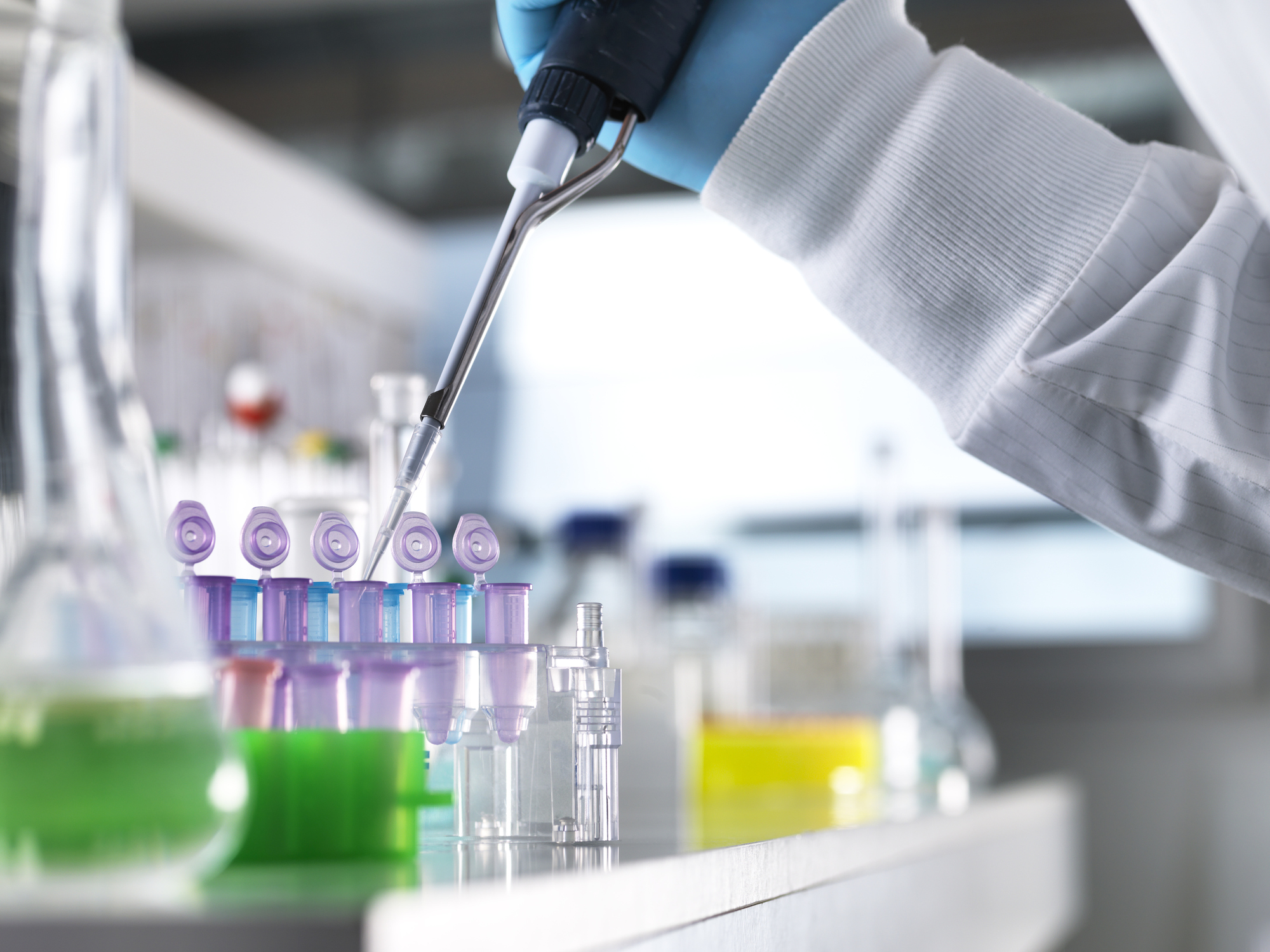 Scientist pipetting a sample into a vial for analytical testing in a chemistry laboratory.