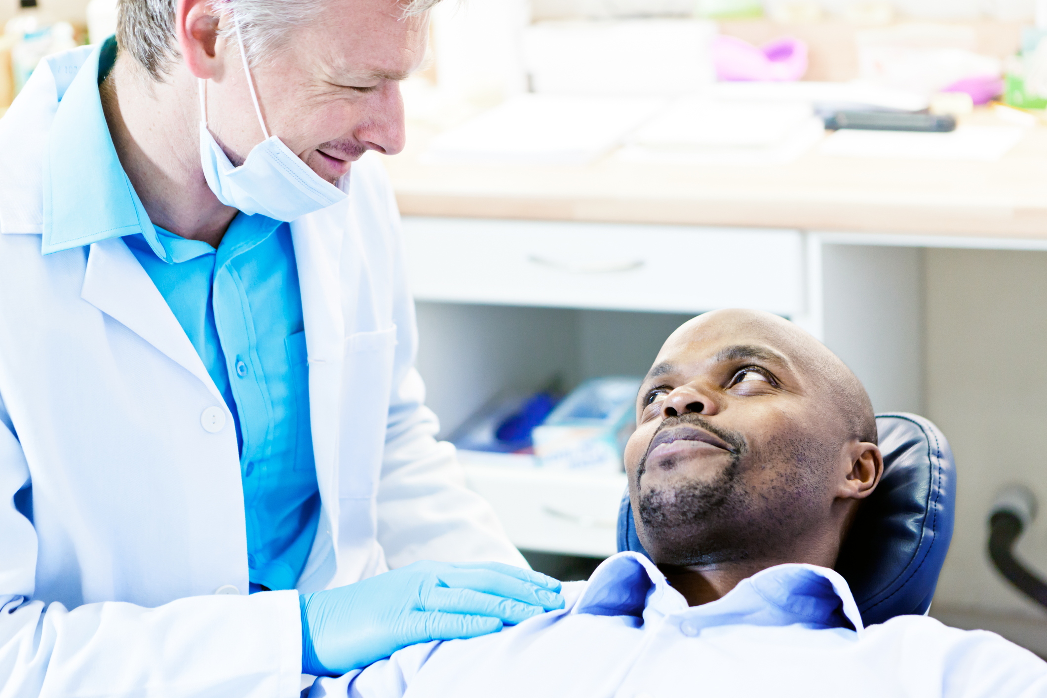 Smiling dentist reassures male dental patient in the chair