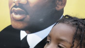 A girl posing with a portrait of Martin Luther King Jr. at the Martin Luther King Jr. Parade.