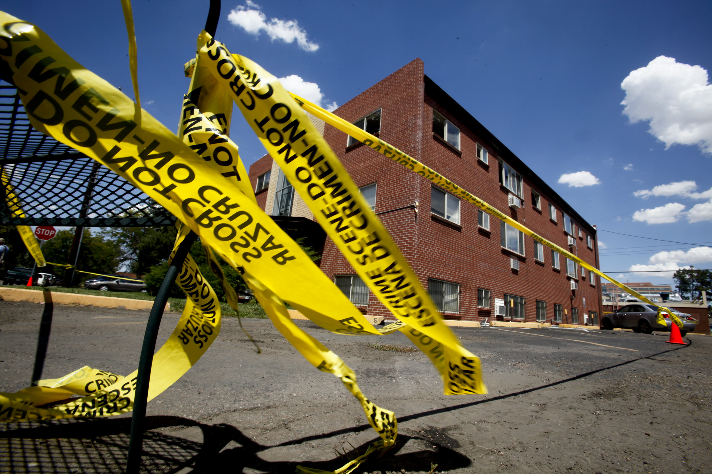 Police tape flutters in the breeze while prosecution teams continue to investigate the apartment co