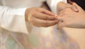 Midsection Of Couple Holding Hands During Wedding