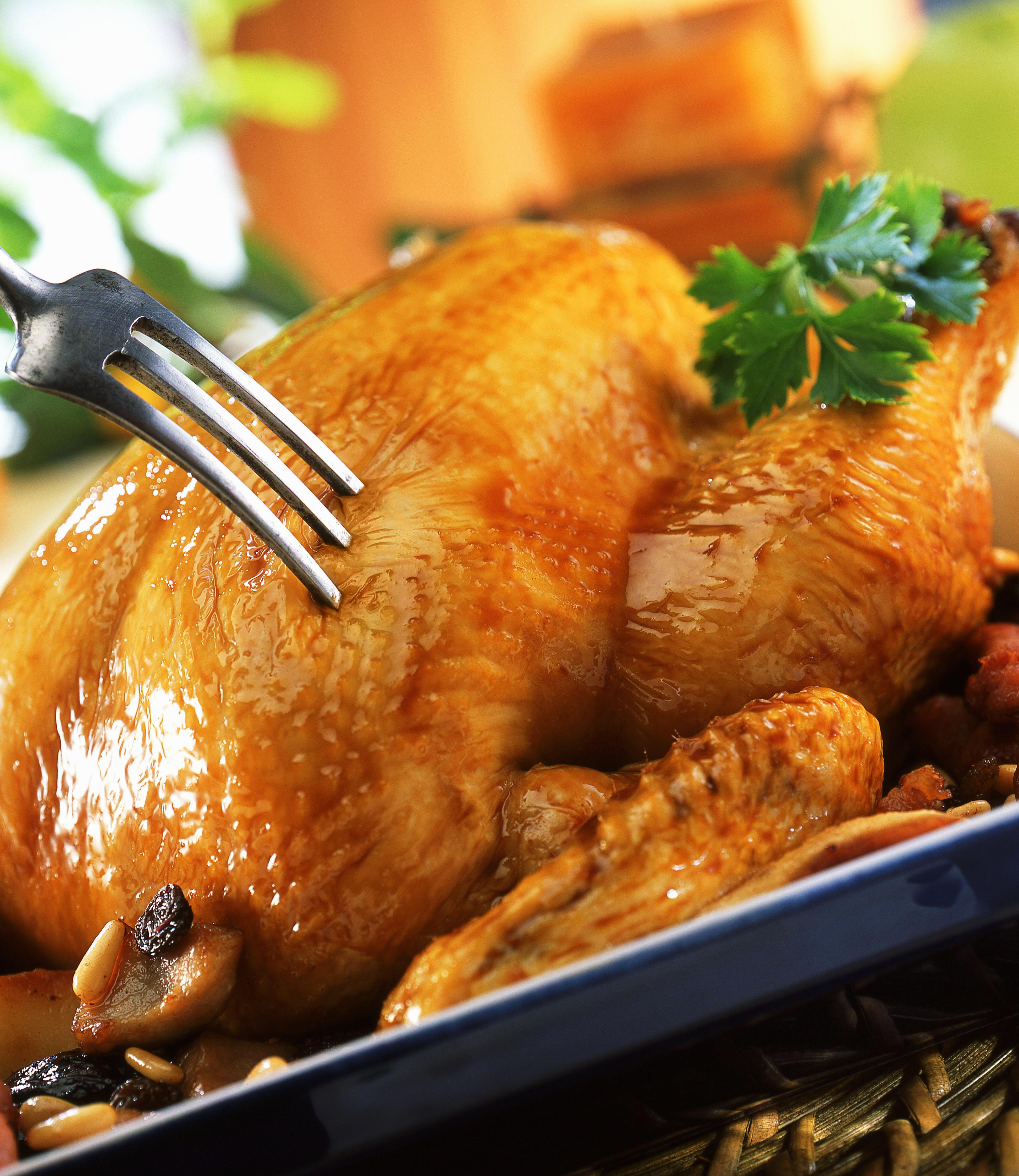 Roasted chicken with fork, close-up