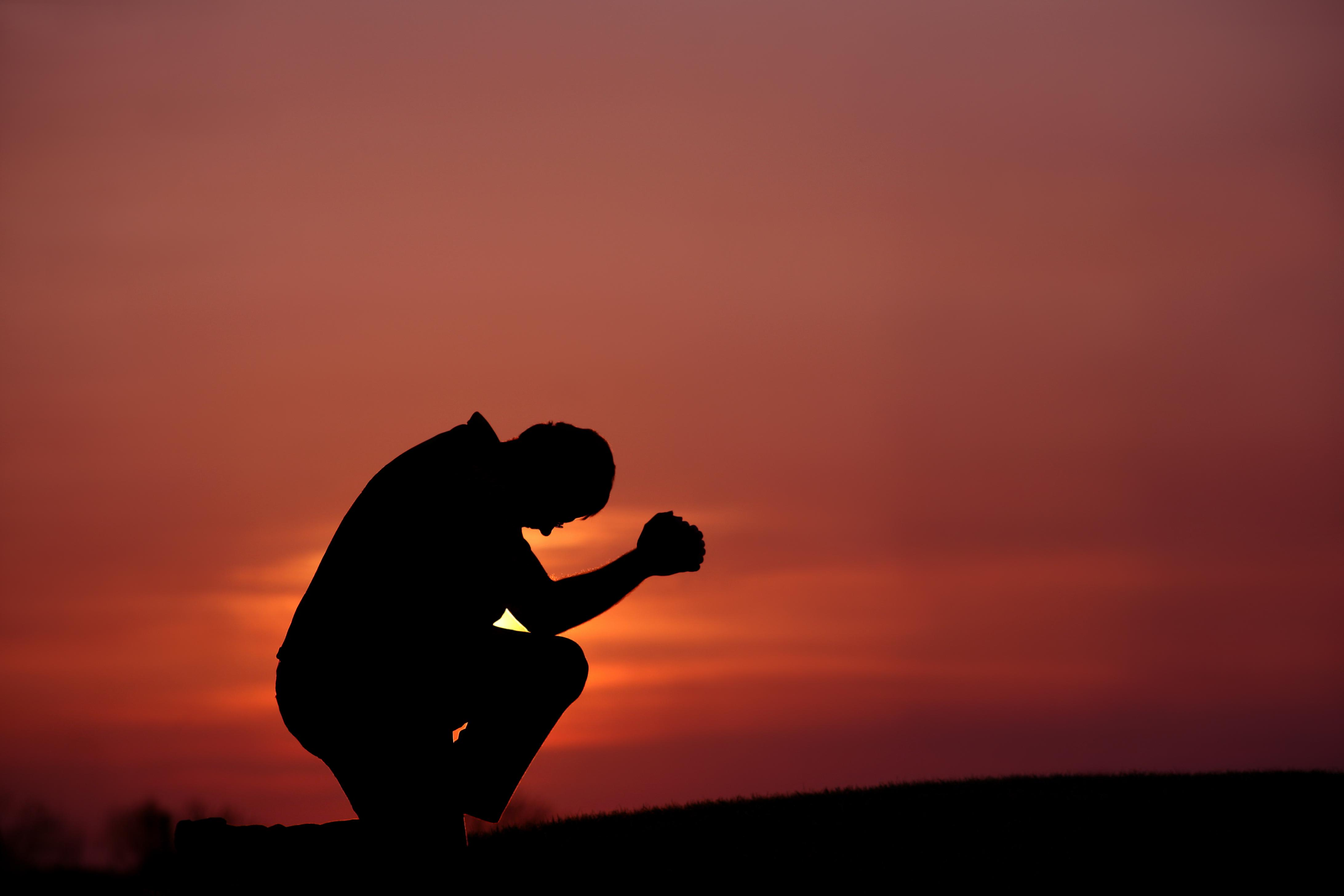 Silhouette of Man Praying at Dusk