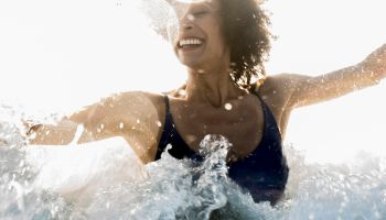 Ocean waves splashing on Mixed Race woman