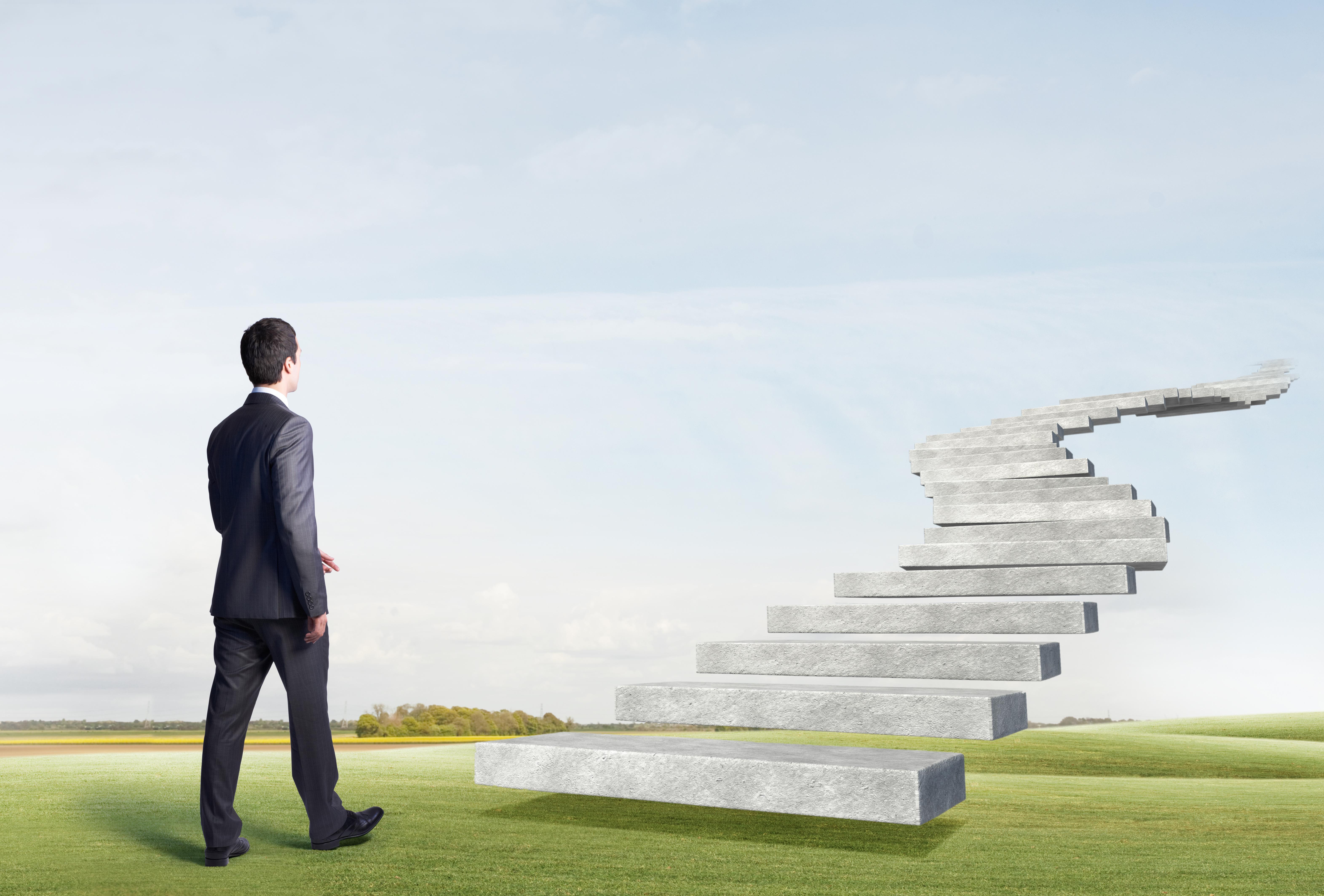 Business man walking toward floating stairs