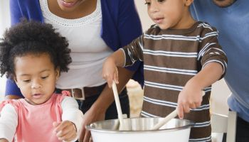Black family baking cookies together