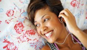 Cheerful, young girl enjoying music through earphones