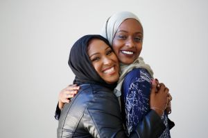 Two young Muslim women wearing hijabs, hugging and smiling