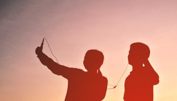 Silhouette Friends Taking Selfie While Listening Music Through Headphones Against Sky During Sunset