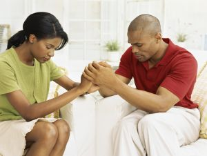 mid adult couple holding hands and praying