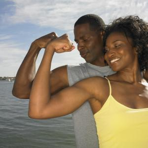 African couple in athletic gear flexing biceps outdoors