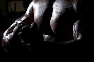 Mid section view of a man flexing his muscles