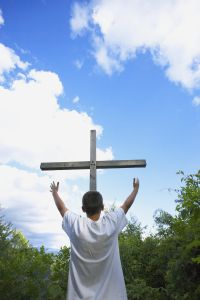 A Teenage Boy With Arms Raised Towards The Cross