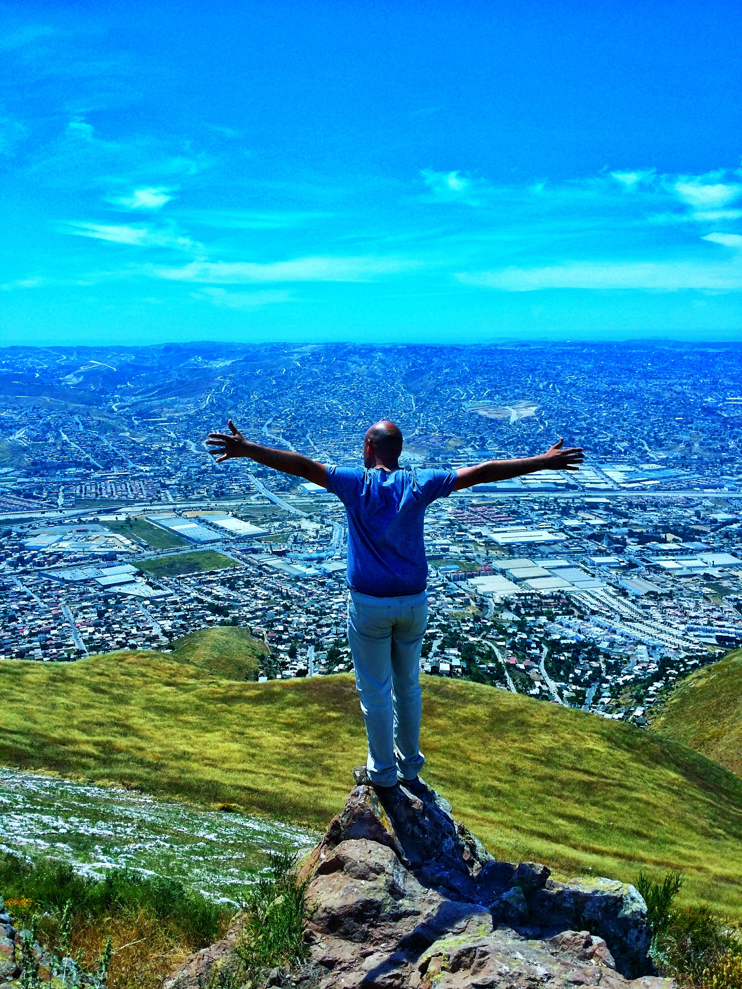 Full Length Of Man With Arms Outstretched Standing On Rock Over Hill Against Cityscape