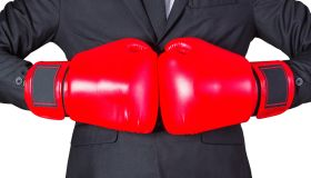 Midsection Of Businessman Wearing Boxing Gloves Against White Background