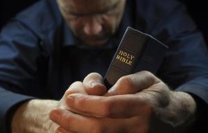 A Man praying holding a Holy Bible.
