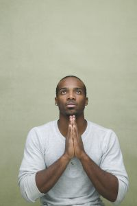 Man facing forward with hands in prayer