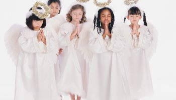 Diverse group of girls wearing angel costumes praying