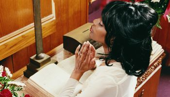 Young Woman Kneeling at an Altar in Church and Praying