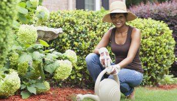 African American woman watering plants