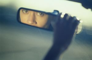 Woman Looking into a Rear-View Mirror