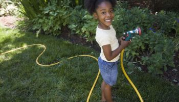 Girl watering plants with hose