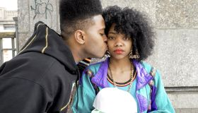 Black male kissing black female with afro
