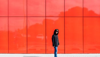 10 year old boy alone on red background