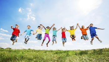 Group of kids having fun while jumping against the sky.