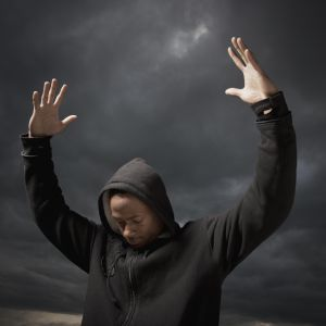 African man with arms raised, storm clouds in distance